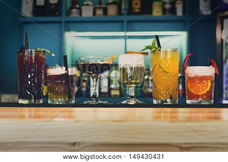 Closeup row of creative sweet exotic alcohol party cocktails in restaurant at bar background. Glasses with beverages on bar table, refreshing drinks with straws, night life concept