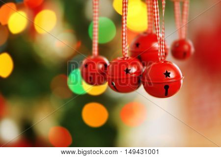 Jingle bells on blurred Christmas lights background, closeup