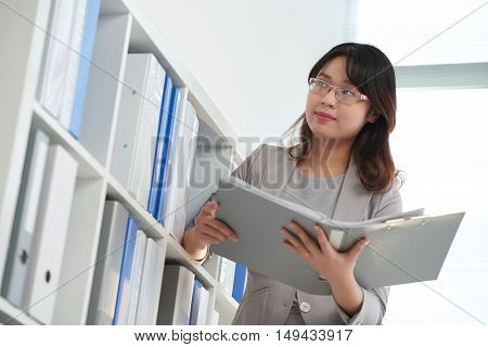Asian female bookkeeper with big binder of documents