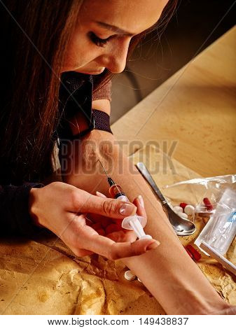 Young woman of drug addict with tourniquet and syringe.