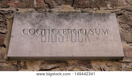 Cogito ergo sum. A Latin philosophical proposition by Rene Descartes usually translated into English as I think, therefore I am. Engraved text.