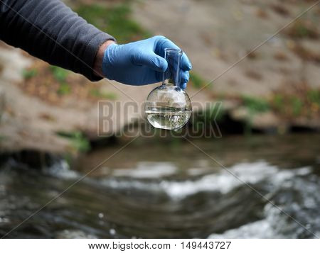 Water Sample. Gloved Hand Collects Water In The Retort. Analysis Of Water Purity, Environment, Ecolo