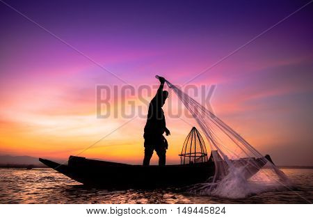 Silhouette of traditional fishermen throwing net fishing inle lake at sunrise time.(The casting people living along the River)