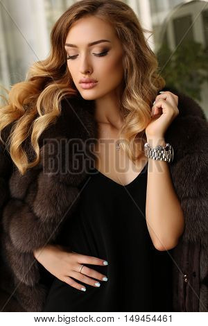 fashion outdoor photo of gorgeous woman with blond hair in luxurious fur coat walking by autumn city