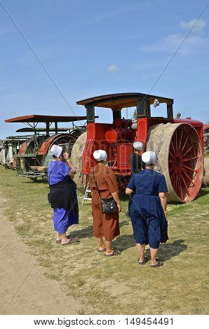 ROLLAG, MINNESOTA, Sept 1. 2016: Unidentified Hutterite Colony women study a restored Avery tractor displayed displayed at the annual WCSTR farm show in Rollag held each Labor Day weekend where 1000's attend.