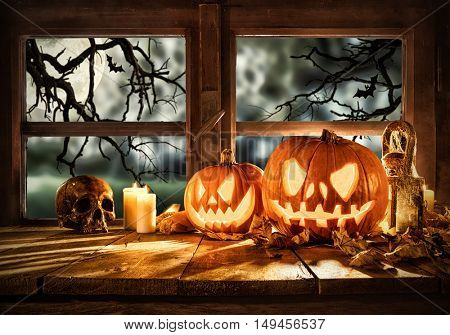 Spooky halloween pumpkins on wooden planks, placed in front of window with scary background