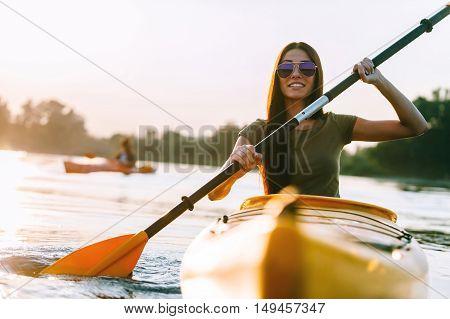 Nice day on kayak. Beautiful young smiling woman kayaking on river