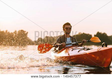 Kayaking on river. Handsome young smiling man splashing water while kayaking on river