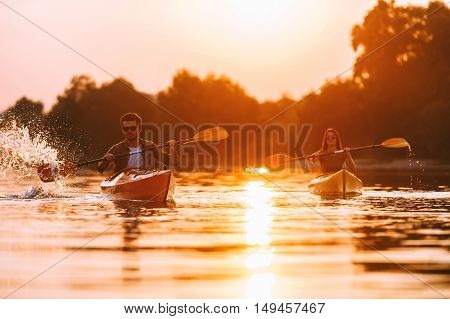 Couple kayaking together. Confident young couple kayaking on river together with sunset in the backgrounds
