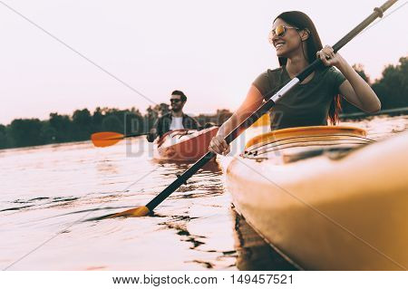 Enjoying nice time on river together. Low angle view of beautiful young couple kayaking on river together and smiling with sunset in the background