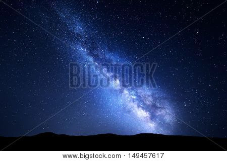 Milky Way. Night colorful landscape with stars. Starry sky with hills at summer. Space background with galaxy at mountains. Nature background with blue milky way. Universe