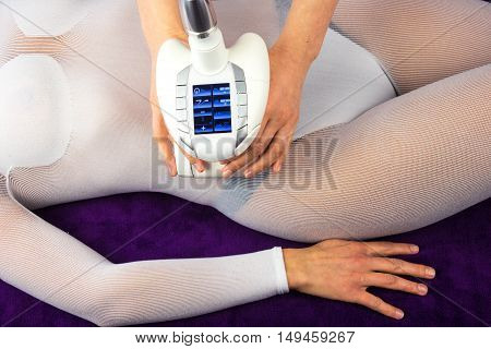 Female body in special white suit having anti cellulite massage with spa apparatus