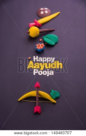 happy dussehra or happy vijayadashmi or happy aayudha pooja greeting card made using a photograph of colourful clay models of ancient indian armour used in Ramayana and Mahabharata poster