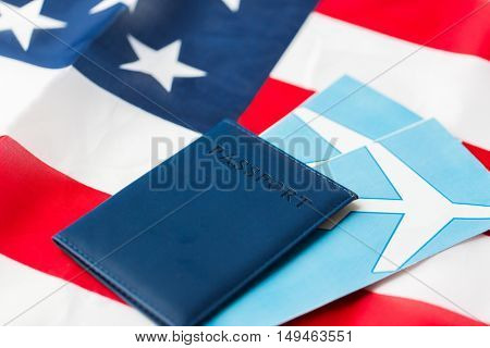 travel, tourism, emigration and visa concept - american national flag, passport and air tickets