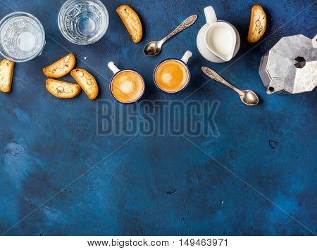Coffee espresso in cups with italian cantucci, cookies and milk in jug over dark blue painted plywood background, top view, copy space, . Food frame concept