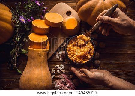 Pumpkin millet porridge with pumpkin in the background. Still life. eating pumpkin millet porridge with milk hands breakfast on a wooden background.
