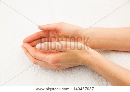 Beautiful caucasian female hands on white towel