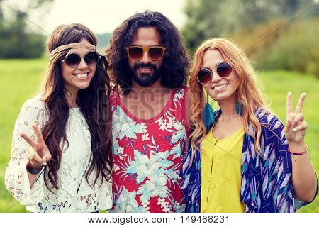 nature, summer, youth culture, gesture and people concept - smiling young hippie friends in sunglasses showing peace hand sign on green field