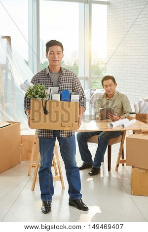 Vietnamese businessman with big cardboard box of belongings