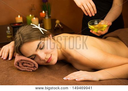 Beautiful woman in spa salon having spa therapy aroma oil procedure with hands of masseur