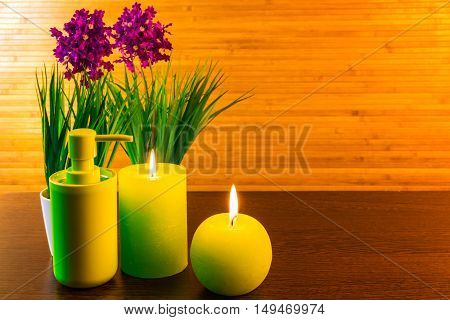 Green spa bath products concept with candles, flowers, towel with ribbon