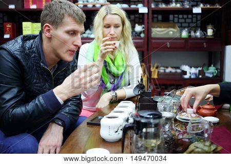 Woman and man taste Chinese tea and sniff tea during tea ceremony