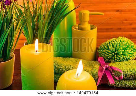 Macro view of green spa bath products concept with candles, flowers, grass