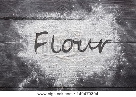 Baking class or recipe concept on dark background, sprinkled wheat flour with flour text copy space. Baking preparation, top view on wooden board or table. Cooking dough or pastry.