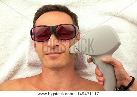 Relaxing man with glasses in spa salon laying on white towel