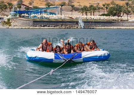 Group Of Young People Floating On An Inflatable Attraction
