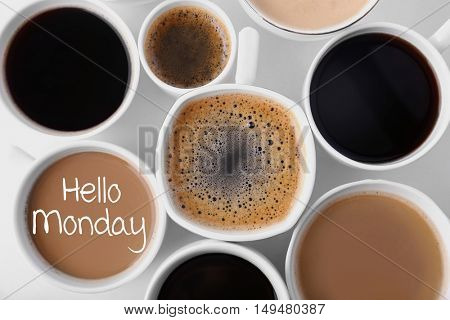 Text HELLO MONDAY and cups of aromatic coffee, closeup