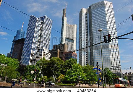 Frankfurt-on-Main, Germany - May 9, 2014. View of Financial district in Frankfurt, with commercial buildings, including Commerzbank Tower, Eurotower, Bank of America tower and Taunusturm, with tram and people.