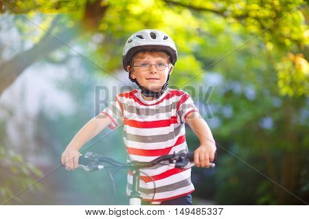 Happy  kid boy of 6 years in helmet having fun with riding of bicycle. Active child making sports with bike in nature. Safety, sports, leisure with kids concept.