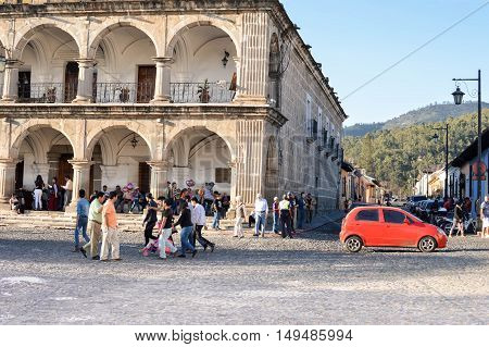 Antigua Guatemala - February 15 2015: People are seen walking the cobble stone roads by the main Plaza of Antigua Guatemala