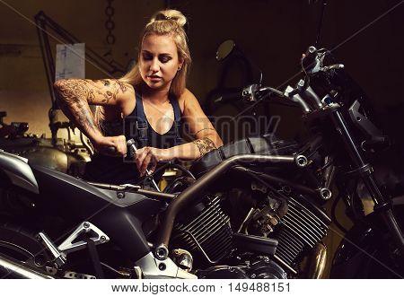 Blond Woman Mechanic Repairing A Motorcycle In A Workshop