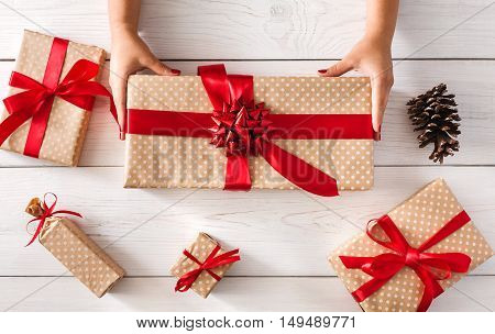 DIY hobby. Woman's hands give wrapped christmas holiday handmade present in paper with red ribbon. Present box, decoration of gift on white wooden table, top view with copy space