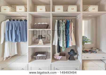 Modern Wooden Wardrobe With Clothes Hanging On Rail In Walk In Closet