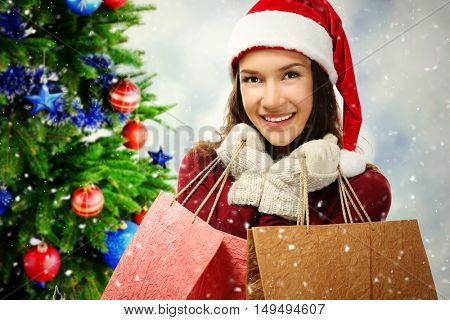 Beautiful happy woman with shopping bags and decorated Christmas tree on blurred lights background. Christmas holiday concept.