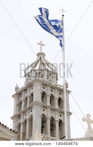 Lefkes Paros Greek Island church cathedral wth Greece national flag in wind