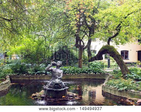 park with pond and statue on fountain off shopping street Drottninggatan Stockholm Sweden Europe