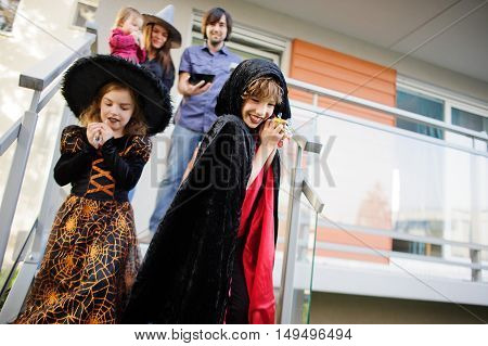 Trick or Treat. Two children in suits of evil forces have come to demand sweet. The young family friendly meets children on a threshold of the house. Sweets are received. Children love Halloween.