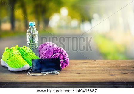 Pair of yellow green sport shoes towel water smart pone and headphones on wooden board. In the background forest or park trail.Accessories for running sport.