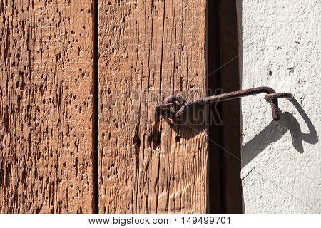 Rusted Latch Hook On Rough Wooden Door