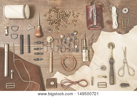 Leather craft tools on wooden background - toned image