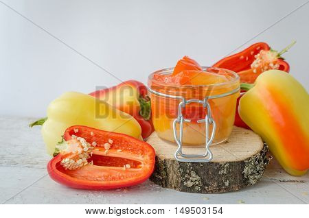Bell pepper preserved in a glass jar with fresh peppers on white wooden background. Homemade marinated in oil red pepper. Glass jar with conserved roasted sweet paprika. Selective focus. Copy space.