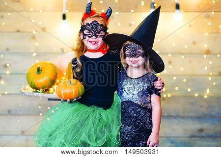 Happy deamon and witch children during Halloween party playing around the table with pumpkins