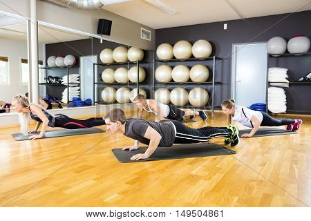 Full length of male and female friends performing pushups on mat in gym