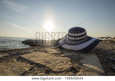 Fashionable straw sunhat at the seaside lying on a shelf of rock overlooking the ocean with the evening or morning sun low on the horizon in the background conceptual of a summer vacation.