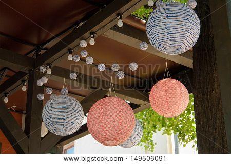 Paper chandelier on street restaurant or cafe.