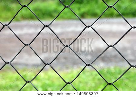 mesh netting galvanized on the background of the road and grass